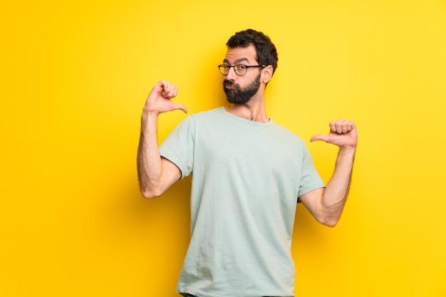誇りを持って自己満足の概念でひげと緑のシャツを持つ男
