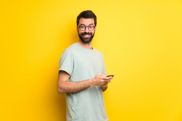 携帯電話でメッセージを送信するひげと緑のシャツを持つ男