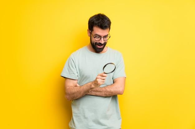 虫眼鏡を持ってひげと緑のシャツを持つ男