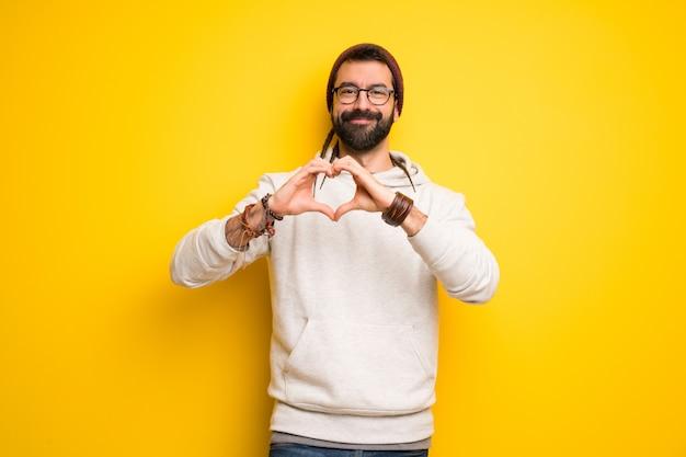 Хиппи человек с дредами, делая символ сердца руками