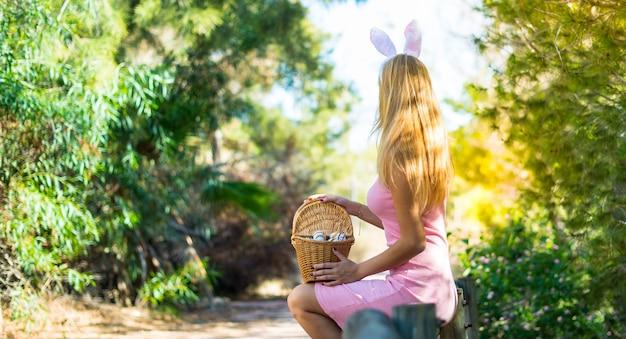 カラフルなイースターエッグとバニーの耳を着ている若いブロンドの女性