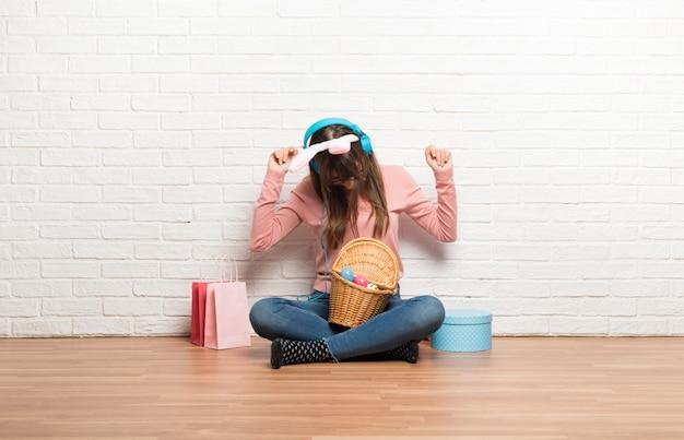 イースター休暇のヘッドフォンで音楽を聴くとダンスの床の上に座ってのバニーの耳を持つ女性