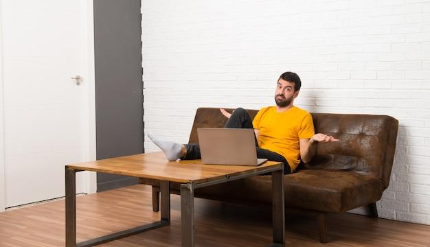 Человек с ноутбуком в комнате несчастлив и разочарован чем-то, потому что не понимает что-то