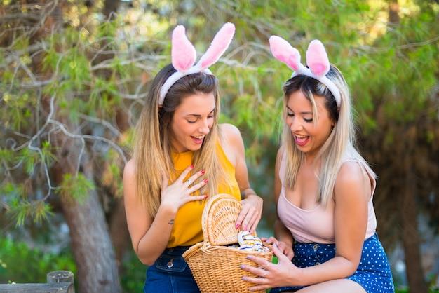 バニーの耳を着て、屋外でカラフルなイースターエッグを持つ若い女性