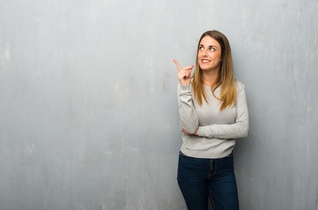 素晴らしいアイデアを指していると見上げるテクスチャ壁の若い女性