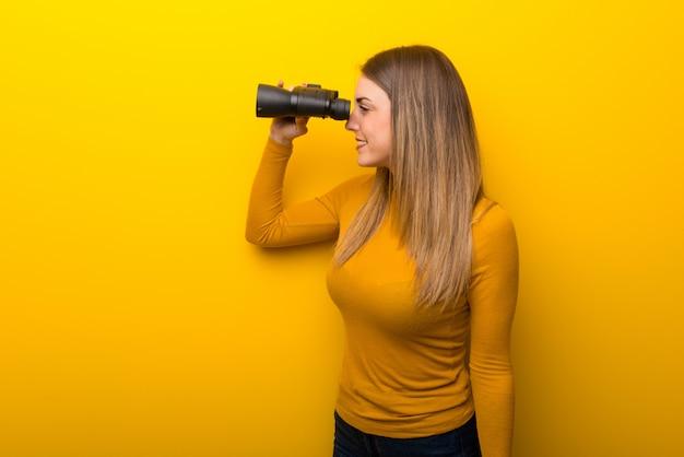 黄色の背景と双眼鏡で遠くに見ている若い女性