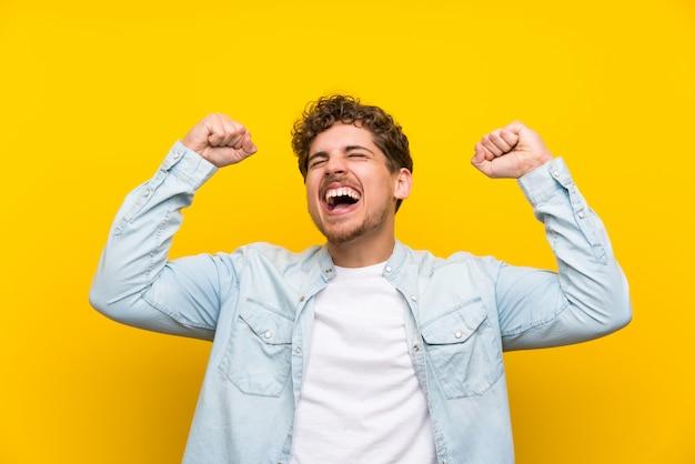 勝利を祝っている孤立した黄色の壁の上の金髪の男