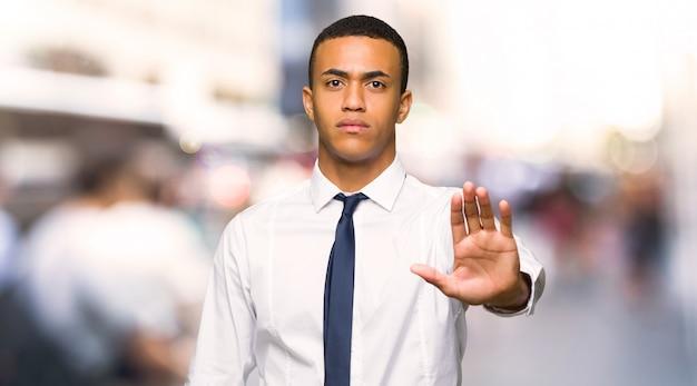都市で間違っていると考える状況を否定する停止ジェスチャーを作る若いアフロアメリカンビジネスマン