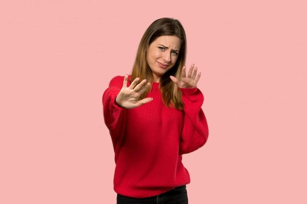 Молодая женщина с красным свитером нервной и испуганно протягивая руки вперед на изолированном розовом фоне