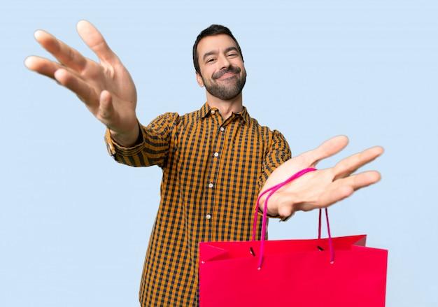 提示し、孤立した青い背景に手で来ることを勧めて買い物袋を持つ男