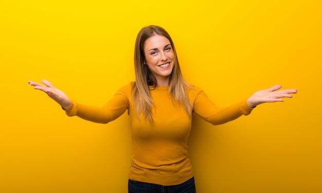 黄色の背景に提示し、手に来るように招待の若い女性