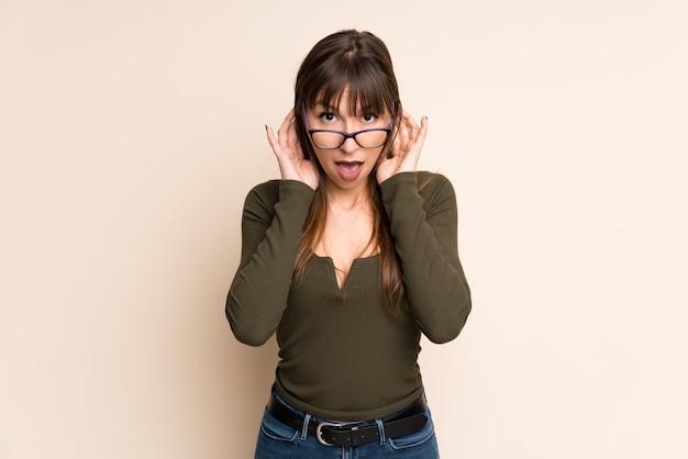メガネと驚きの黄土色の背景に若い女性