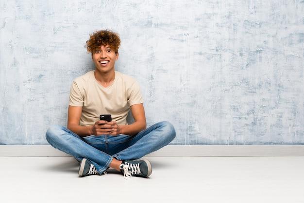 携帯電話でメッセージを送信する床の上に座っている若いアフリカ系アメリカ人