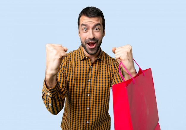 孤立した青い背景に勝者の位置で勝利を祝う買い物袋を持つ男