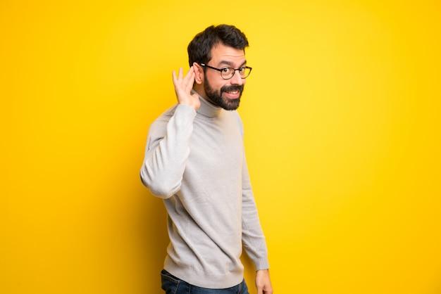 Человек с бородой и водолазкой слушает что-то, положив руку на ухо