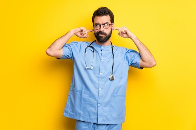 Хирург доктор человек, охватывающий оба уха руками