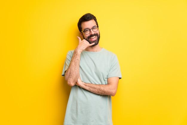 電話のジェスチャーを作るひげと緑のシャツを持つ男。私にバックサインイン