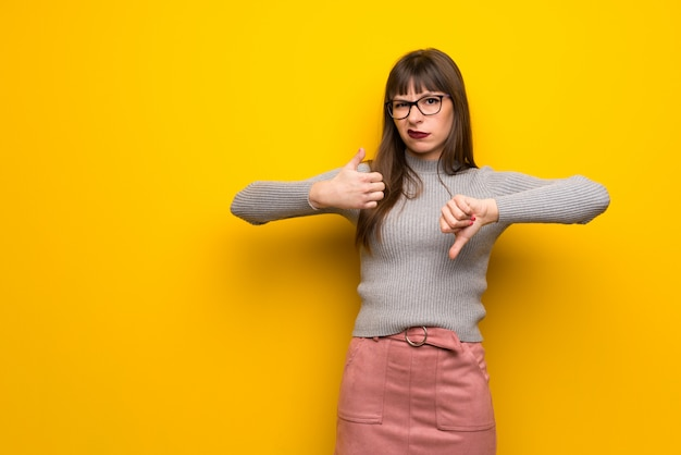 悪い面のサインを作る黄色の壁の上の眼鏡を掛けた女性。はいかどうかは未定