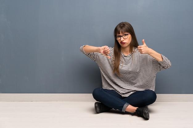 悪い面のサインを作る床に座ってメガネを掛けた女性。はいかどうかは未定