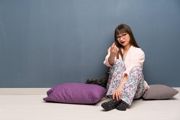 床にパジャマを着て手に来ることを勧めている女性。あなたが来たことを幸せに