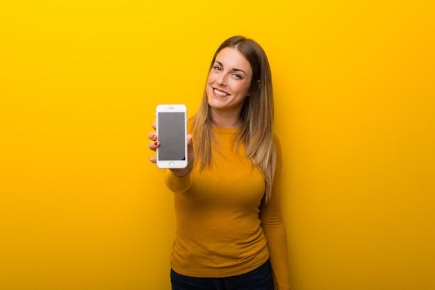 Молодая женщина на желтом фоне, показывая на мобильный