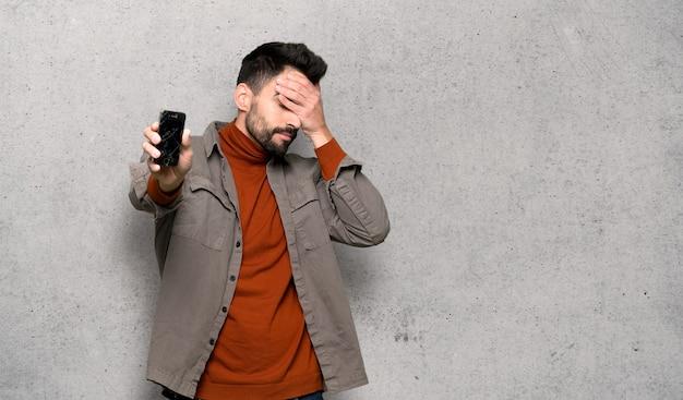織り目加工の壁の上の問題を抱えた持株壊れたスマートフォンとひげを持つハンサムな男