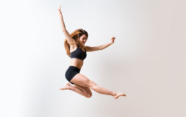 孤立した白い壁の上の若いダンス少女