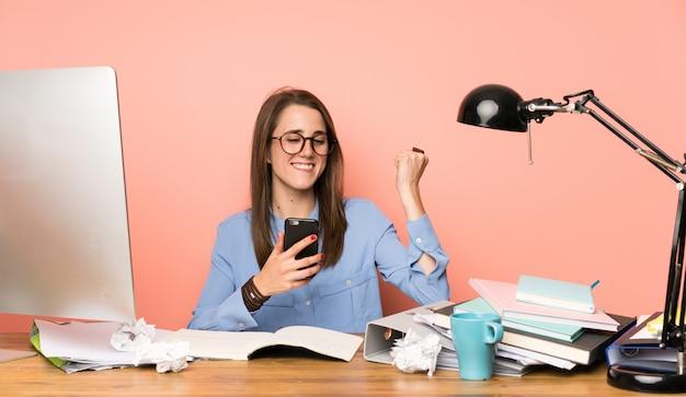 勝利の位置で携帯電話を持つ若い学生の女の子