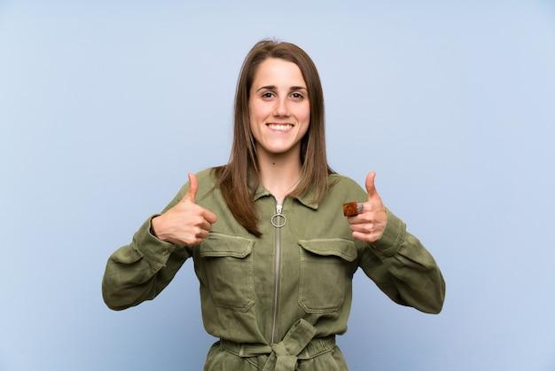 ジェスチャー親指を与える孤立した青い壁を越えて若い女性