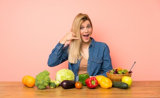 電話のジェスチャーを作る多くの野菜を持つ若いブロンドの女性。私にバックサインイン