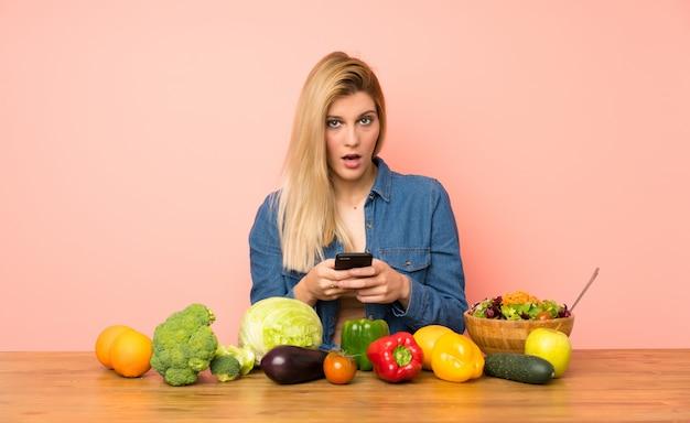 驚いて、メッセージを送信する多くの野菜を持つ若いブロンドの女性
