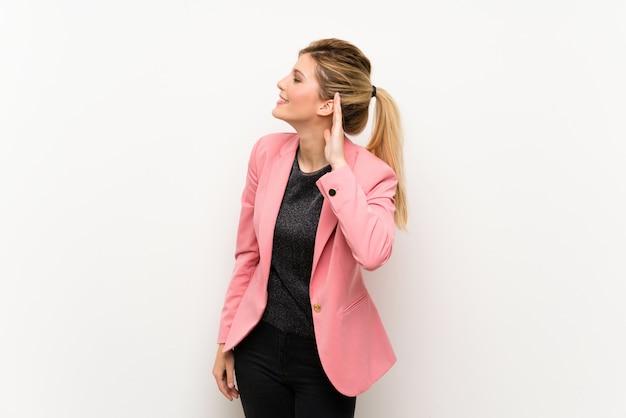 Молодая блондинка в розовом костюме слушает что-то, положив руку на ухо