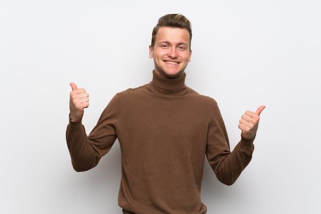 両手で親指ジェスチャーを与えると笑みを浮かべて孤立した白い壁に金髪の男
