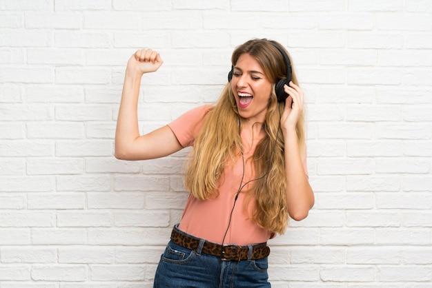 ヘッドフォンで音楽を聴く白いレンガの壁を越えて若いブロンドの女性