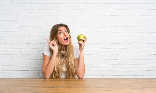 思考のリンゴと若いブロンドの女性