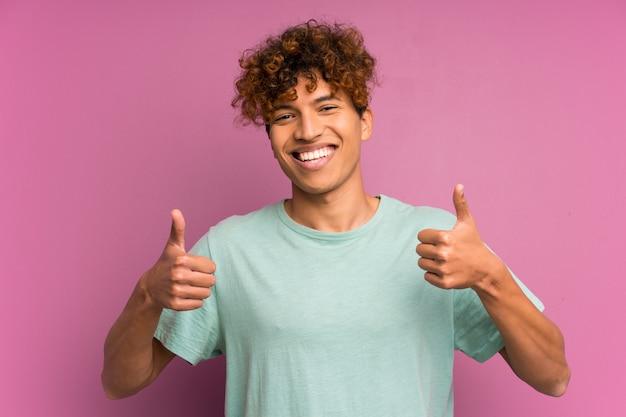 ジェスチャー親指を与える若いアフリカ系アメリカ人男性の壁
