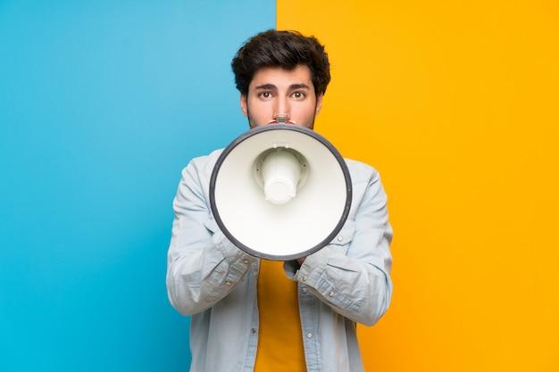 Красивый мужчина кричит в мегафон