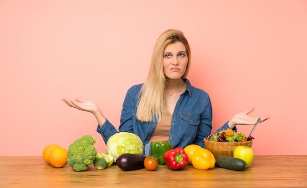 Молодая блондинка с множеством овощей несчастна, что-то не понимаю