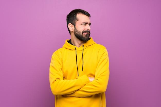 混乱の表情と黄色のスエットシャツを持つハンサムな男