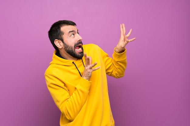 緊張と怖い黄色のスウェットシャツを持つハンサムな男