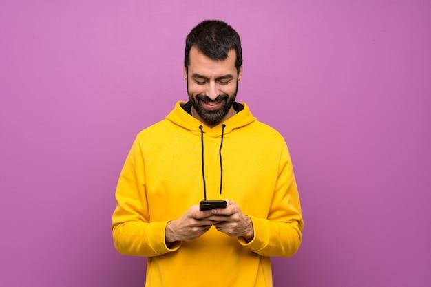 携帯電話でメッセージを送信する黄色のスエットシャツを持つハンサムな男