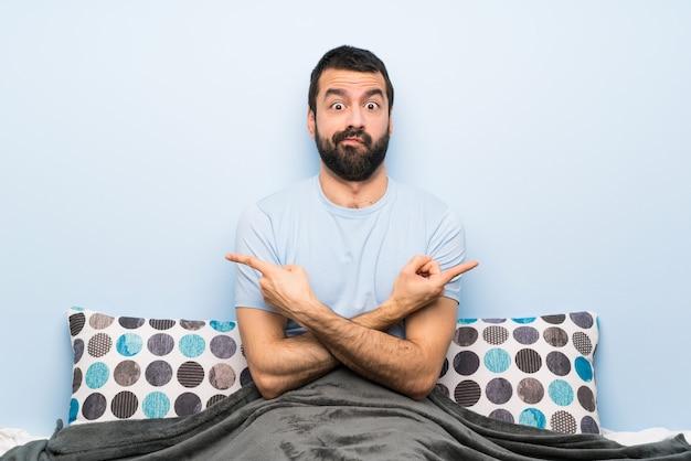 疑問を抱いて外側を指しているベッドの中で男