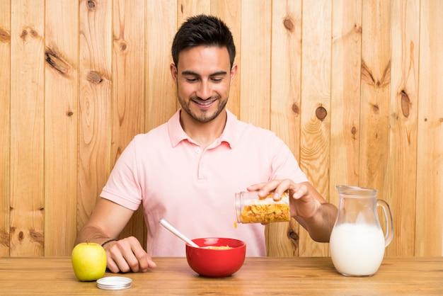 Красивый молодой человек на кухне, имея завтрак