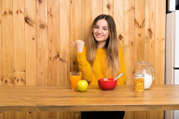 Молодая женщина завтракает на кухне, указывая на сторону, чтобы представить продукт