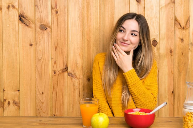 アイデアを考えて台所で朝食を食べて若い女性