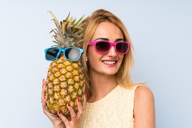 サングラスとパイナップルを保持している若いブロンドの女性