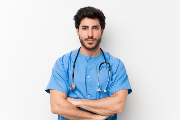 Человек доктора хирурга над изолированной белой стеной держа оружия пересеченный