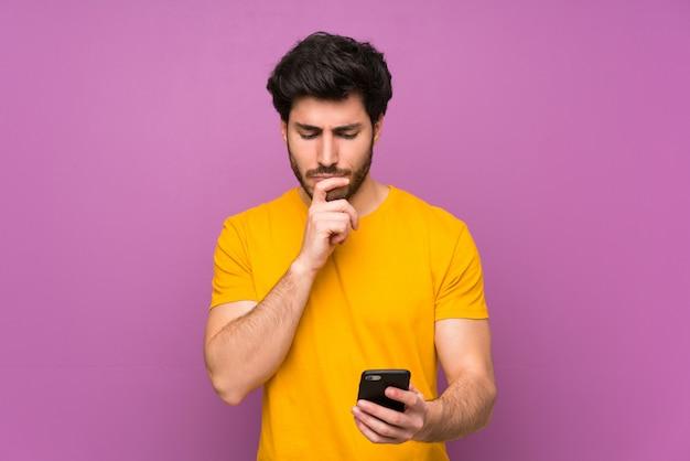 思考とメッセージを送信する孤立した紫色の壁を越えてハンサム