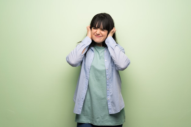 手で耳を覆っている緑の壁を越えて若い女性。欲求不満の表現