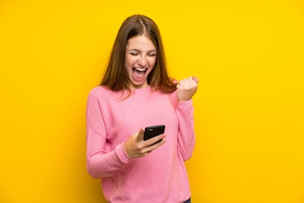 勝利の位置に携帯電話で孤立した黄色の壁の上の長い髪を持つ若い女